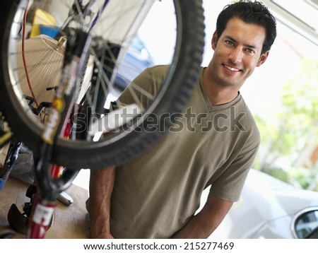 Man repairing bicycle on workbench in domestic garage, smiling, side view, portrait - stock photo