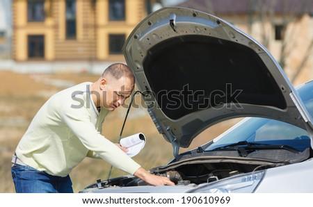 man repairing  broken car on  road reading  user manual - stock photo