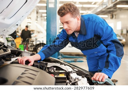 Man repairing car. Concentrated young man in uniform repairing car while standing in workshop