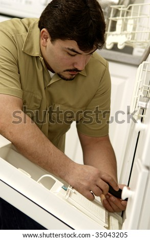 Man repairing dishwasher - stock photo