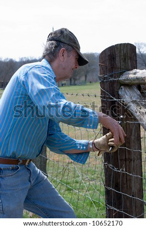 Man repairing fence with fence pliers - stock photo