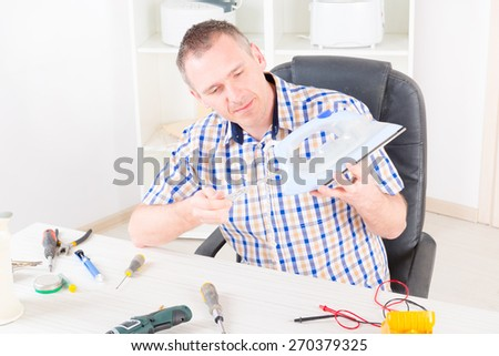 Man repairing iron at home appliance service workshop - stock photo