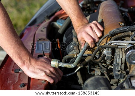 Man repairing motor block of a car