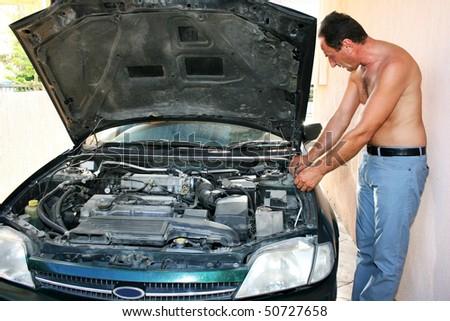 Man repairing old car. - stock photo