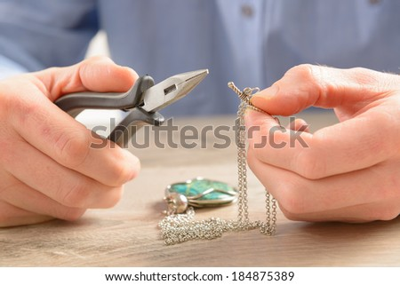 Man repairing or creating jewelry silver chain with pliers - stock photo