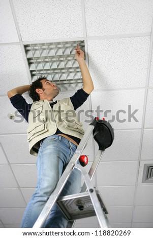 Man replacing ceiling panel - stock photo
