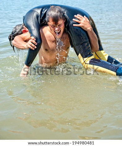 Man rescuing a young female from the sea - stock photo