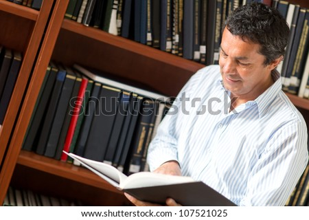 Man researching at the library reading a book - stock photo