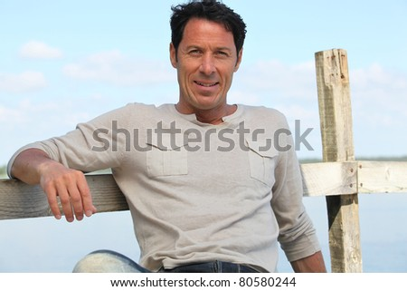 Man resting by the sea - stock photo