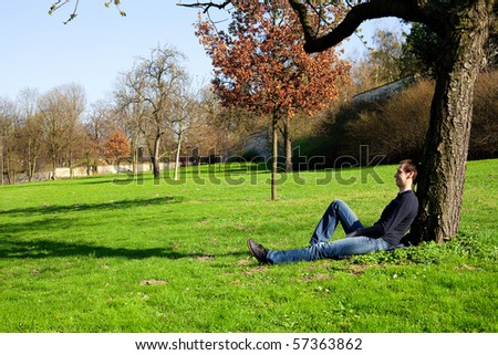 man resting in a tree - stock photo