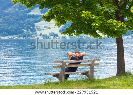 man resting on a bench by the lake, Austria