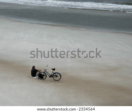 Man resting on an empty beach overlooking the ocean on an overcast day.  A bicycle lays by his side. - stock photo