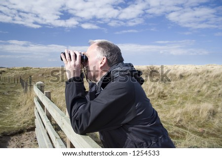 Man resting on fence observing wildlife with binoculars. - stock photo