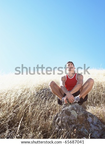 Man resting on hillside rock - stock photo