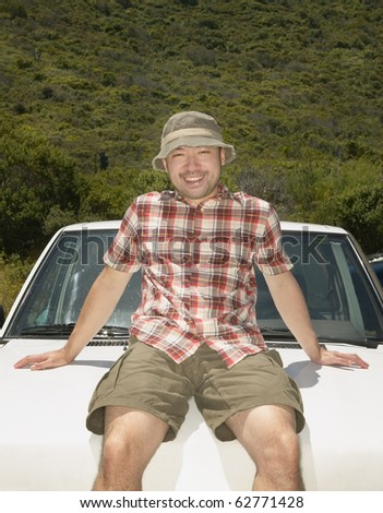 Man resting on hood of his car - stock photo