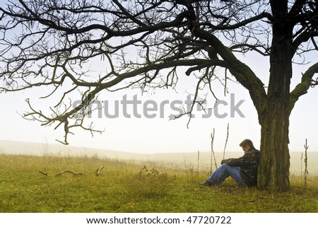 Man resting under a tree. - stock photo