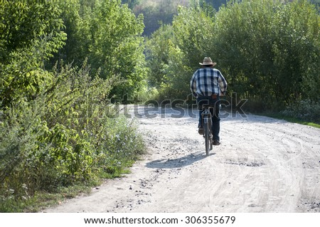 Man ride bicycles in the forest back to camera