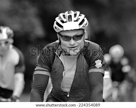 Man riding a bicycle close up in black and white. - stock photo