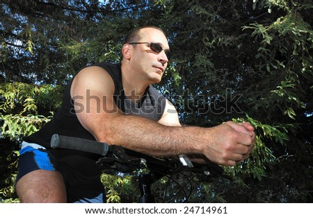 Man Riding a Bike in a Park on a Sunny Day - stock photo