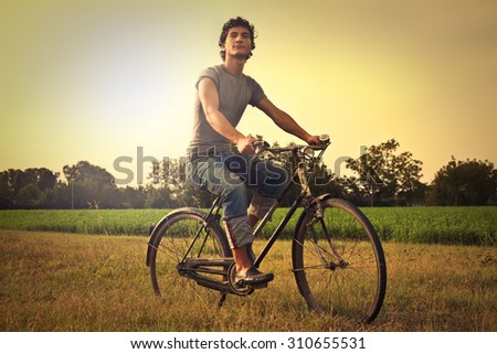 Man riding a bike in the countryside - stock photo