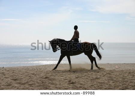 man riding a horse on a beach - stock photo