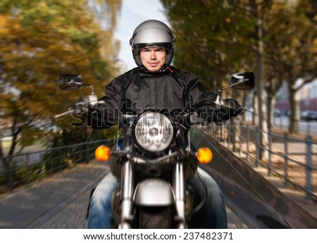Man riding a motorcycle in town fall - stock photo