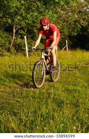 Man riding a mountain bike on a forest trail - stock photo
