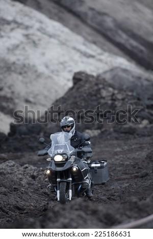 Man Riding Adventure Motorcycle Through Mud Off road - stock photo