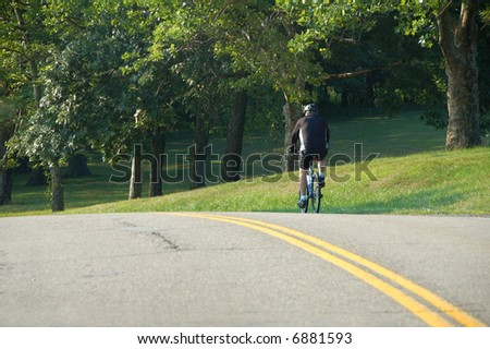 man riding bicycle on street with trees