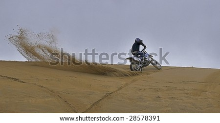 Man riding dirt bike in the sand, spraying up a tail - stock photo