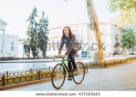 man riding fixed bike in city