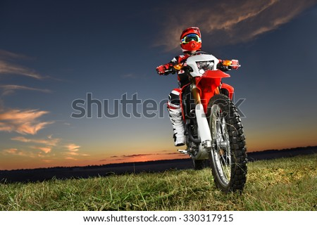 Man riding motocross motorcycle at sunset - With copy space - stock photo