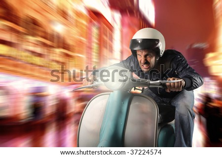 man riding old moped in a city street - stock photo
