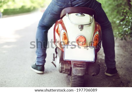 Man riding old retro scooter in a city street. Close up - stock photo
