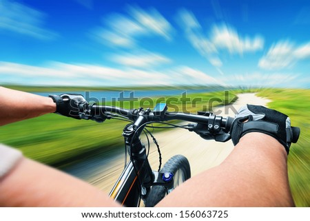 Man riding on a bicycle in a meadow, motion blur