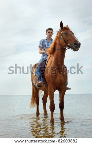 Man riding on a brown horse - stock photo