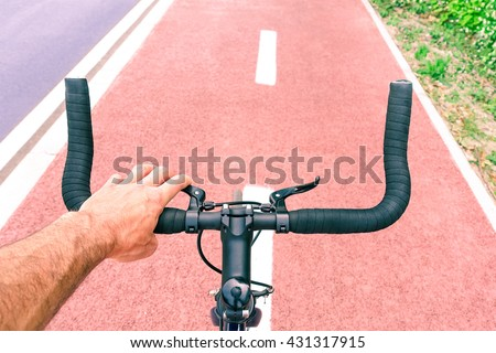 Man riding sport bike top view on handle bar and road perspective - Male hand on bicycle brakes on urban cycle path - Green concept of everyday transport for healthy lifestyle and environment respect - stock photo