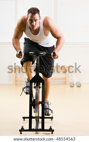 Man riding stationary bicycle in health club - stock photo