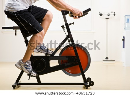 Man riding stationary bicycle in health club