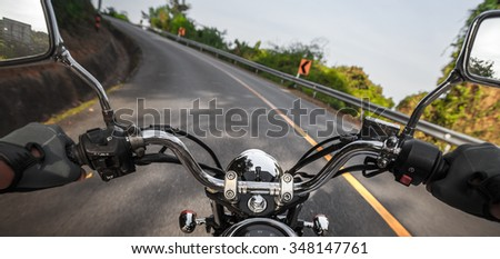 Man riding the motorcycle on the empty asphalt road