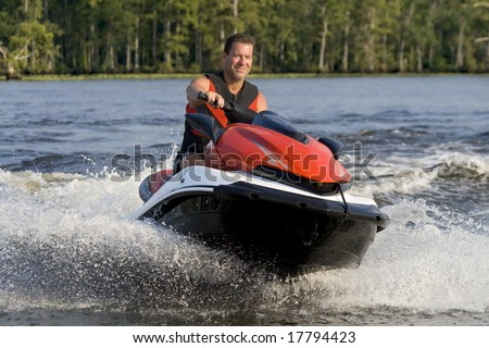 Man riding wave runner in a river, enjoying a nice summer day. - stock photo