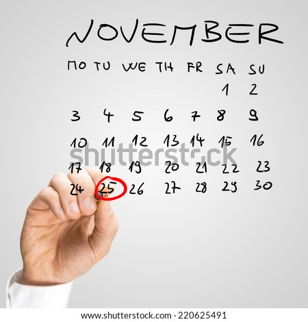 Man ringing the date of the 25th November in red marker pen as a reminder that it is the International Day For The Elimination of Violence Against Women on a hand-drawn calendar.