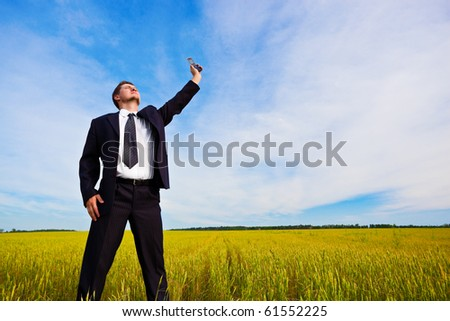 man rising up phone on field