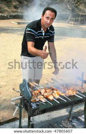 Man roasted barbecue at the charcoal. - stock photo