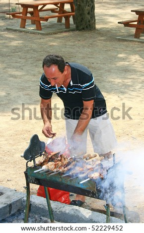Man roasted barbecue on the charcoal. - stock photo