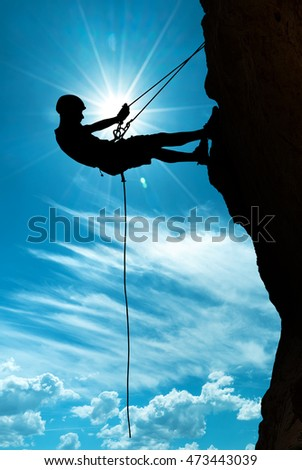 Man rock climber silhouette over blue sunny sky