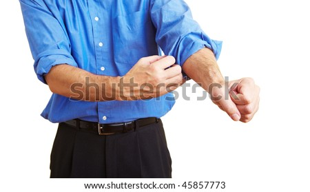 Man rolling up his blue shirt sleeves - stock photo