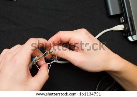 man rolls a network cord - stock photo