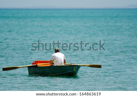 Man row a small wooden rowboat dinghy over calm water in the ocean. - stock photo