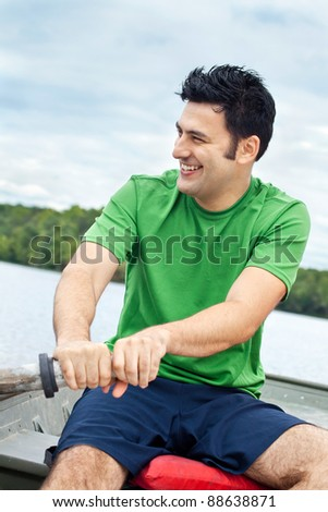 Man rowing a rowboat on a lake - stock photo